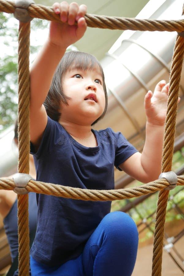Curso de obstáculo de escalada da corda da criança chinesa asiática olhado pelo adulto fotografia de stock