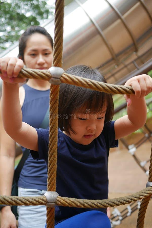 Curso de obstáculo de escalada da corda da criança chinesa asiática olhado pelo adulto fotos de stock