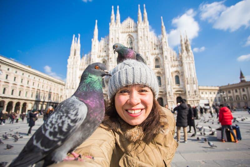 Curso do inverno, férias e conceito dos pássaros - mulher engraçada nova que toma o selfie com os pombos perto dos di de Milan Ca imagens de stock
