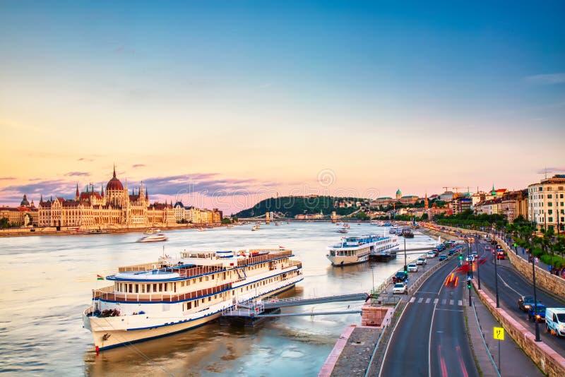 Curso e conceito europeu do turismo O parlamento e beira-rio em Budapest Hungria com os navios sightseeing durante o por do sol d imagem de stock royalty free