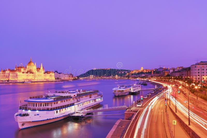 Curso e conceito europeu do turismo O parlamento e beira-rio em Budapest Hungria com os navios sightseeing durante o por do sol a fotos de stock