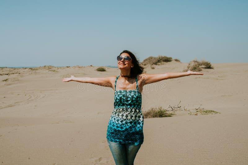 Curso, férias de verão, viagem por estrada e conceito dos povos - óculos de sol da jovem mulher feliz e sol vestindo da apreciaçã fotografia de stock royalty free