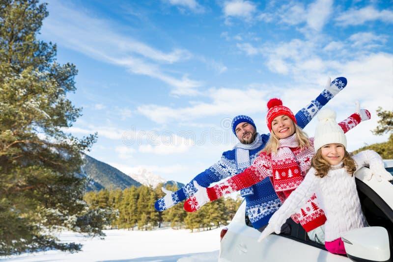 Curso feliz da família pelo carro no inverno imagem de stock
