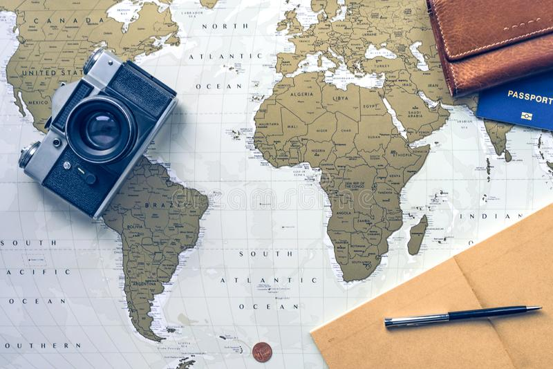 Curso flatlay: carteira, livro de bolso, passaporte, pena, moeda e câmera no mapa do mundo no fundo foto de stock royalty free