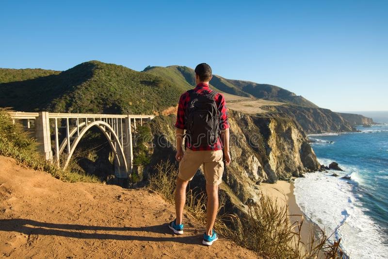 Curso no Big Sur, caminhante do homem com trouxa que aprecia a ponte de Bixby da vista, Califórnia, EUA foto de stock