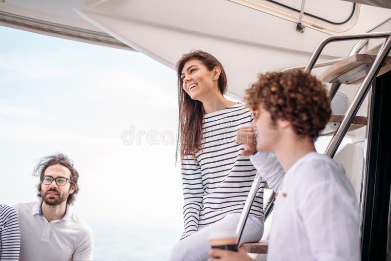 Curso, seatrip, amizade e conceito dos povos - amigos que sentam-se na plataforma do iate fotos de stock royalty free