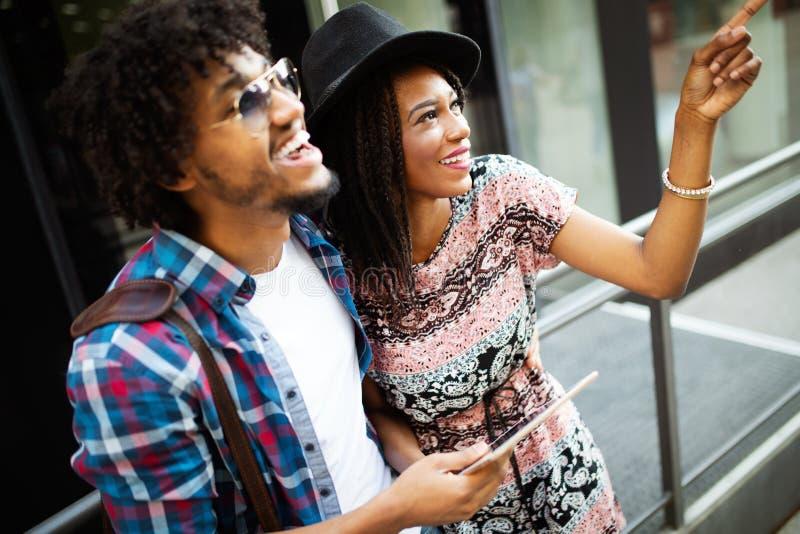 Curso, turismo, f?rias de ver?o, tecnologia e conceito da amizade - par de sorriso com PC da tabuleta fotografia de stock royalty free