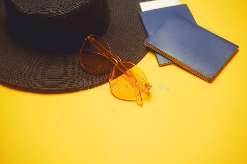 cursos Chapéu, 2 passaportes, bilhetes planos e vidros em um fundo alaranjado Lugar vazio para o texto Discontos do curso feriado foto de stock royalty free