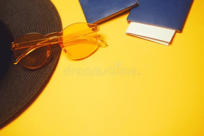 cursos Chapéu, 2 passaportes, bilhetes planos e vidros em um fundo alaranjado Lugar vazio para o texto Discontos do curso feriado fotos de stock royalty free
