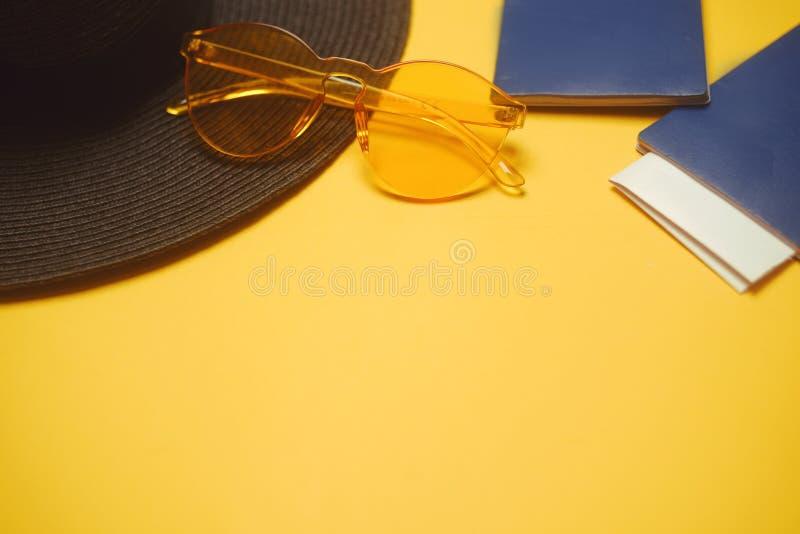 cursos Chapéu, 2 passaportes, bilhetes planos e vidros em um fundo alaranjado Lugar vazio para o texto Discontos do curso feriado foto de stock