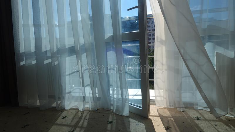 Curtains on the window and open balcony door in the apartment stock photos