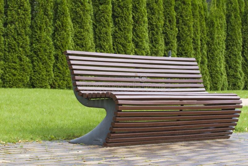 A curva à moda deu forma à mobília exterior marrom do banco de madeira no parque como a imagem de fundo fotografia de stock royalty free