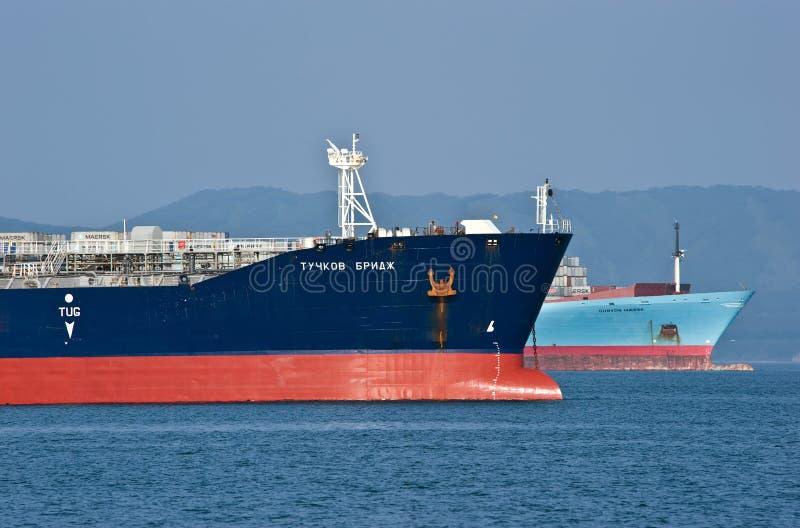 A curva de um navio Gunvor Maersk de Tuchkov do petroleiro dos huges da ponte e de recipiente no ancorado nas estradas Louro de N fotos de stock royalty free