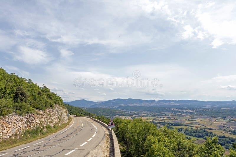 Curva del camino de la montaña sobre el bosque y campos agrícolas en campo francés imagen de archivo