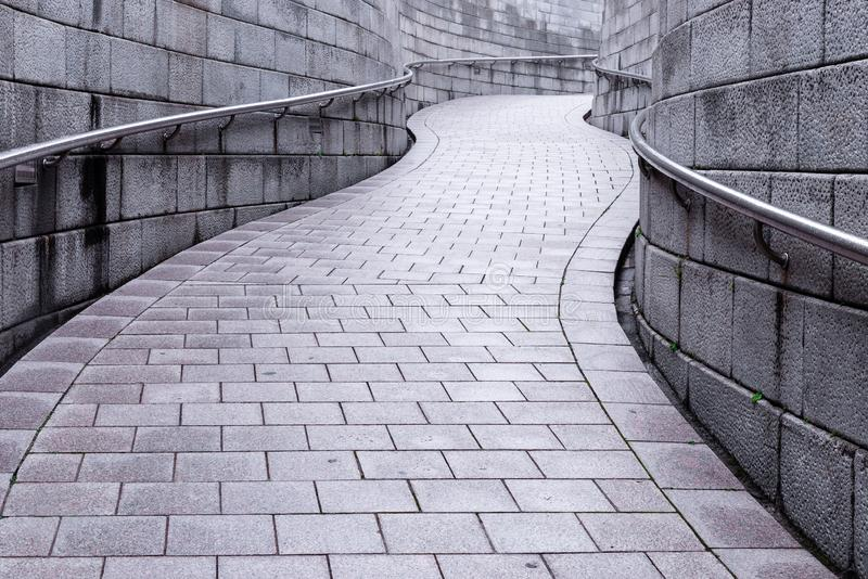 Curva della via grigia di colore con la parete di pietra nel giorno piovoso fotografia stock libera da diritti