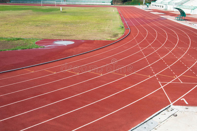 Curva e linha na pista de atletismo com tampa de borracha da textura foto de stock
