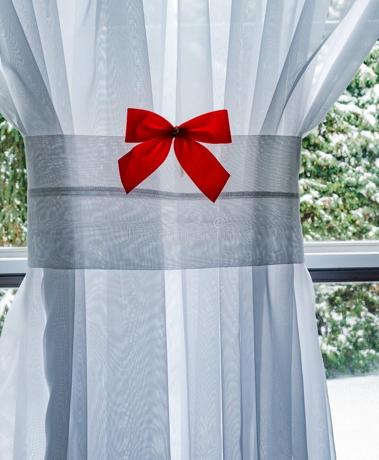 Curva vermelha de Chrismas na cortina branca com placa de janela e a árvore nevado imagens de stock