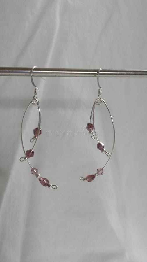 Curvado cuelgue los pendientes con los cristales púrpuras y el alambre plateado plata de la memoria imagen de archivo libre de regalías