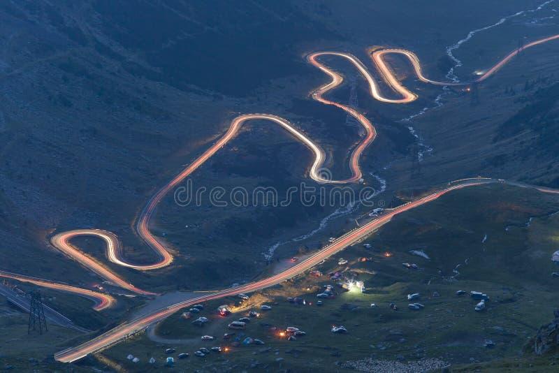 Curvado y yéndose volando el camino en la noche, tráfico en la montaña de Transfagarasan imagenes de archivo