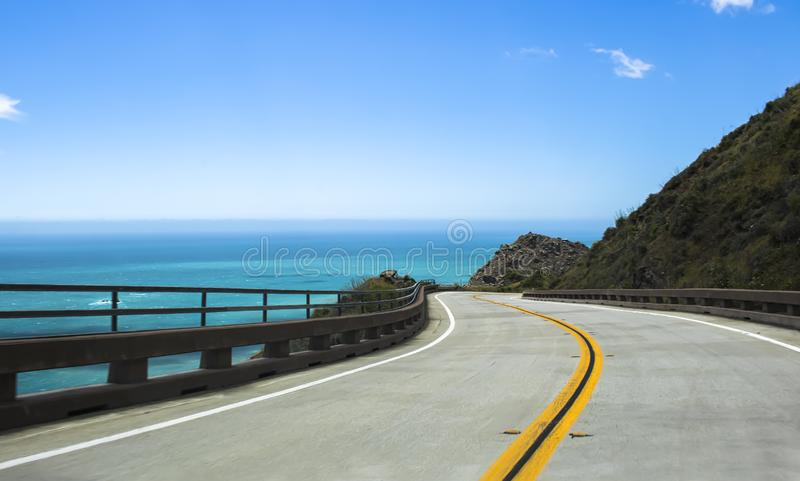 Curvando a estrada ao longo do mar azul na estrada 1 de Califórnia imagem de stock