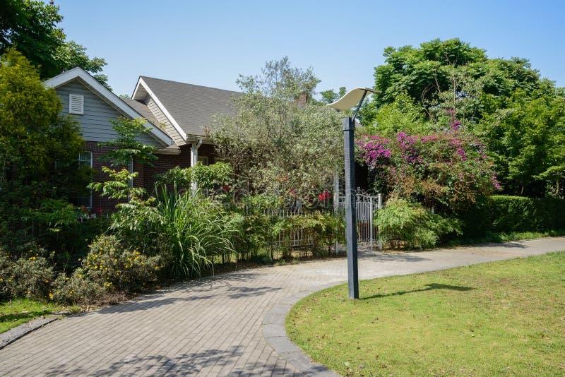 Curvando o trajeto e o gramado gramíneo antes das casas arborizados no verão ensolarado fotografia de stock royalty free