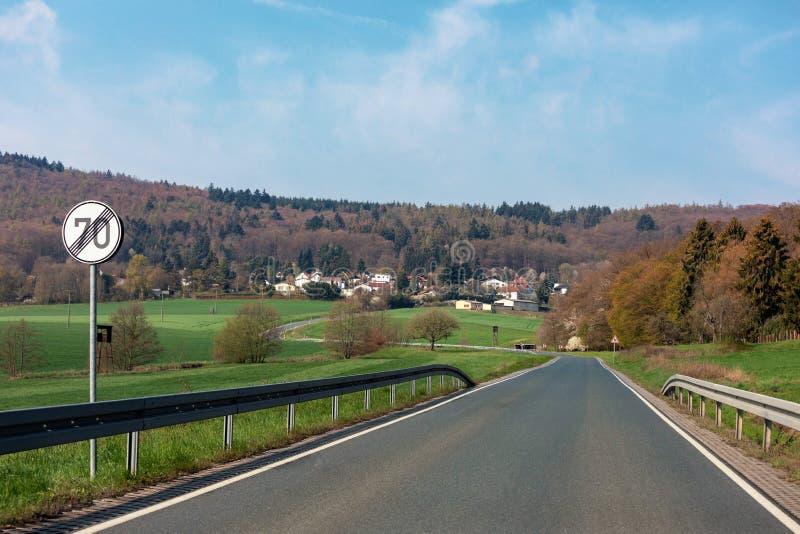 Curvando strada fra i campi e gli alberi in Germania Langgöns in primavera immagine stock