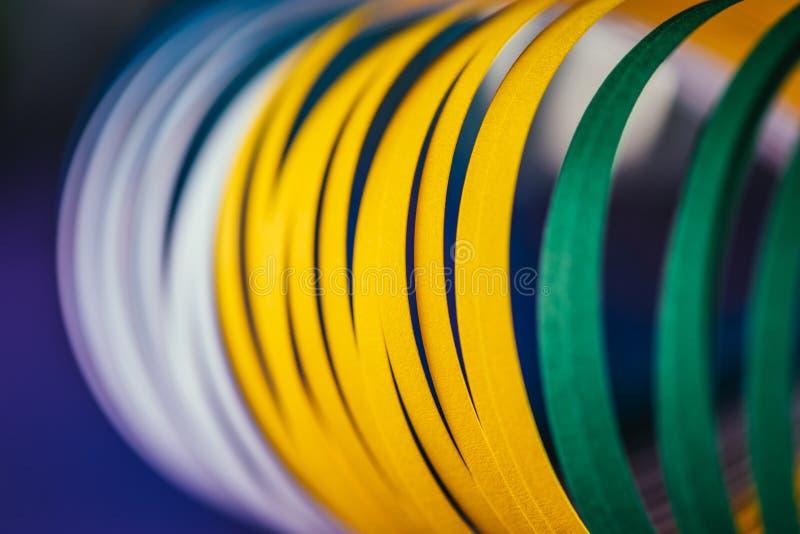 Curvas de papel quilling brancas, verdes e amarelas no azul imagem de stock royalty free