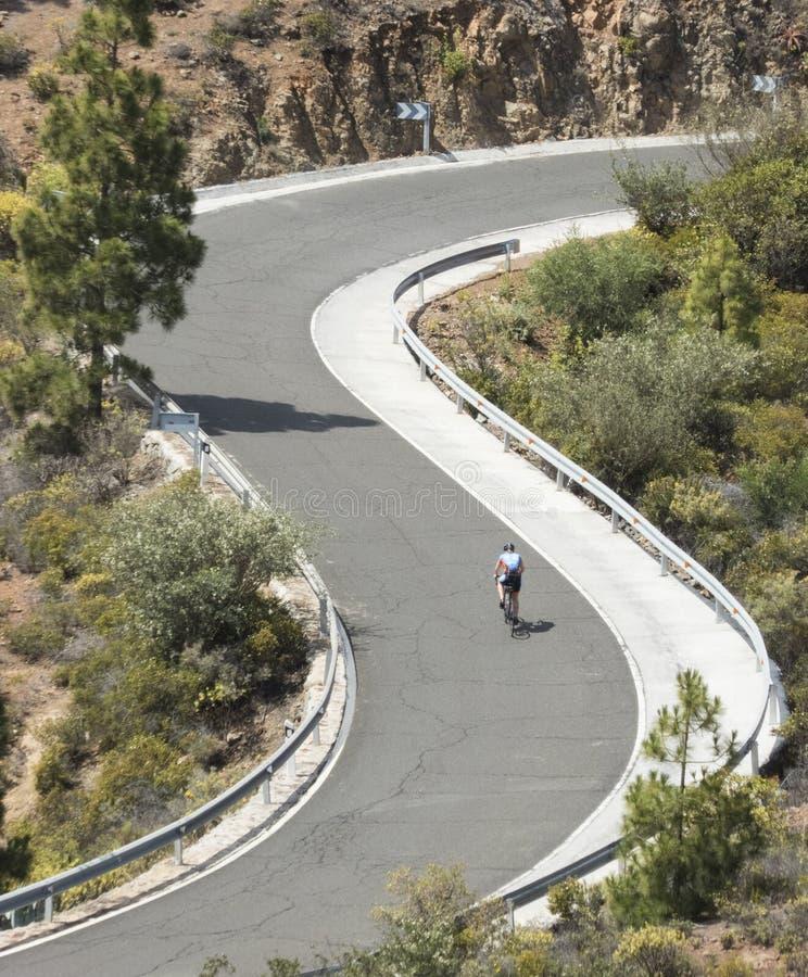 Curvas na estrada com um ciclista fotografia de stock royalty free