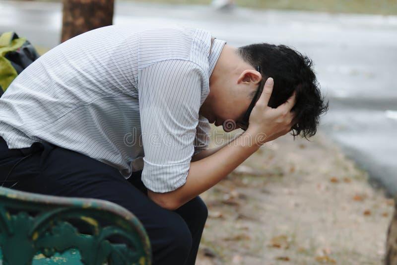 A curvatura asiática nova forçada cansado do homem de negócio dirige para baixo foto de stock