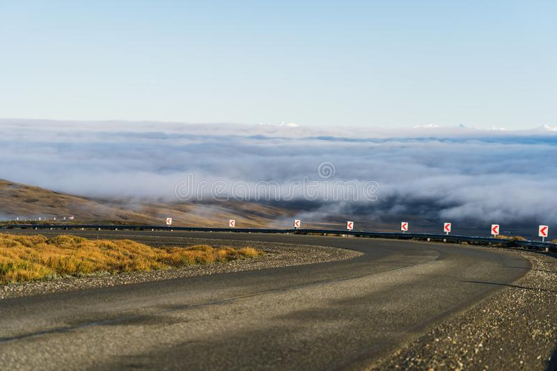 Curve asphalt road with beautiful nature sea of cloud and golden yellow grass in autumn in cloudy blue sky through national park. South Patagonia, Argentina and stock image