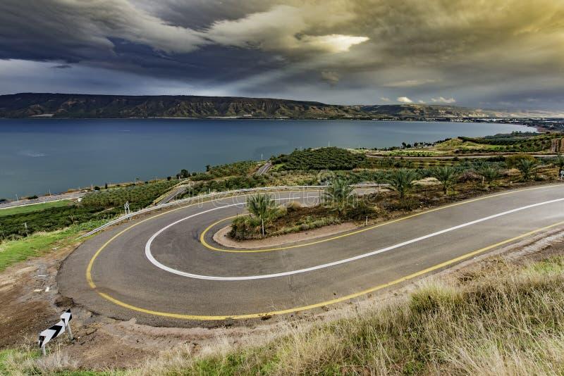 Curve Asphalt Road Near Blue Sea Under Gray Sky royalty free stock photo