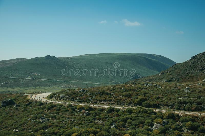Curve road passing through rocky landscape. Curve roadway passing through rocky landscape and green bushes in a sunny day, at the highlands of the Serra da royalty free stock image