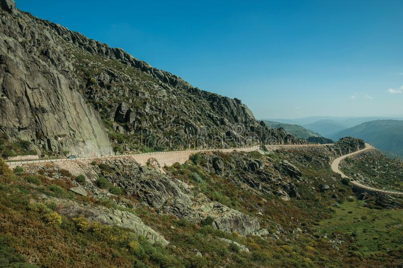 Curve road passing through rocky landscape. Curve roadway passing through rocky landscape and green bushes in a sunny day, at the highlands of the Serra da royalty free stock photos