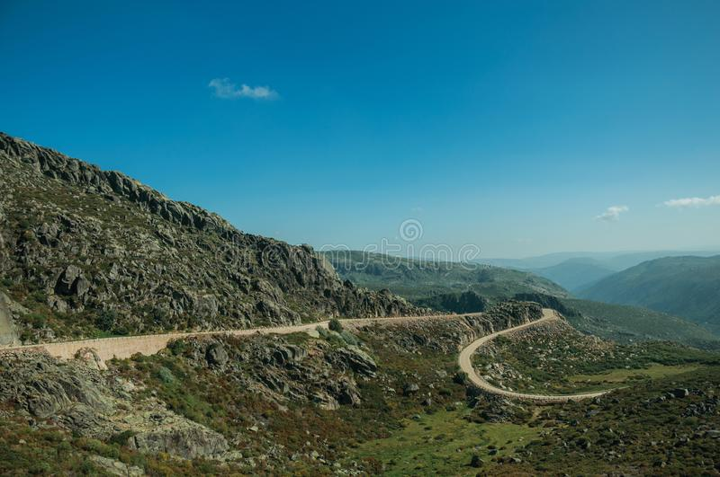 Curve road passing through rocky landscape. Curve roadway passing through rocky landscape and green bushes in a sunny day, at the highlands of the Serra da royalty free stock images