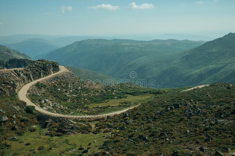 Curve road passing through rocky landscape. Curve roadway passing through rocky landscape and green bushes in a sunny day, at the highlands of the Serra da stock photo