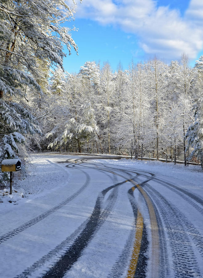 Curve on a Snowy, Icy Road with Tire Tracks. A curvy road with ice and snow and tire tracks from vehicles driving dangerously stock images