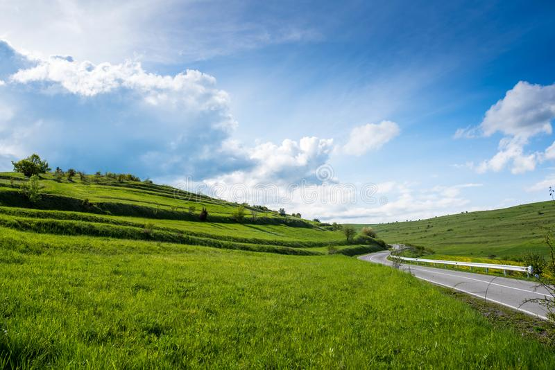 Curved asphalt road on green hills at springtime , dramatic blue sky royalty free stock images