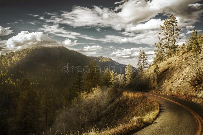 Curved Asphalt Road Between Mountains stock photos