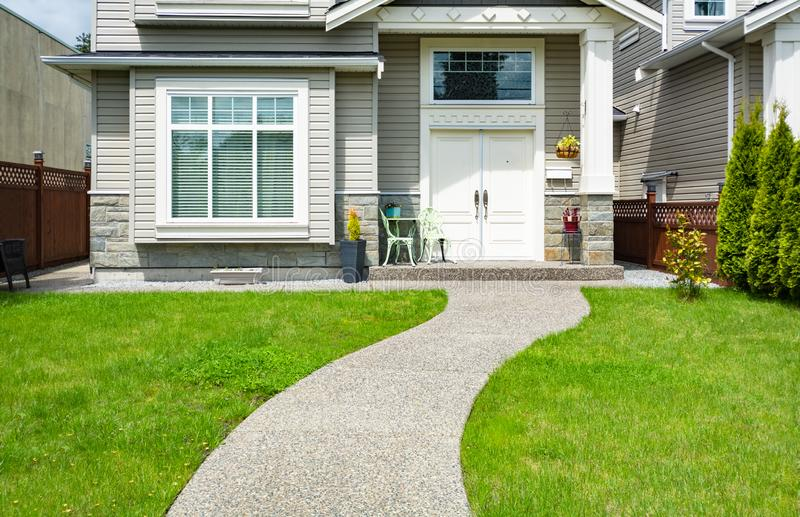 Curved concrete pathway over green lawn to the main entrance of small house royalty free stock photography