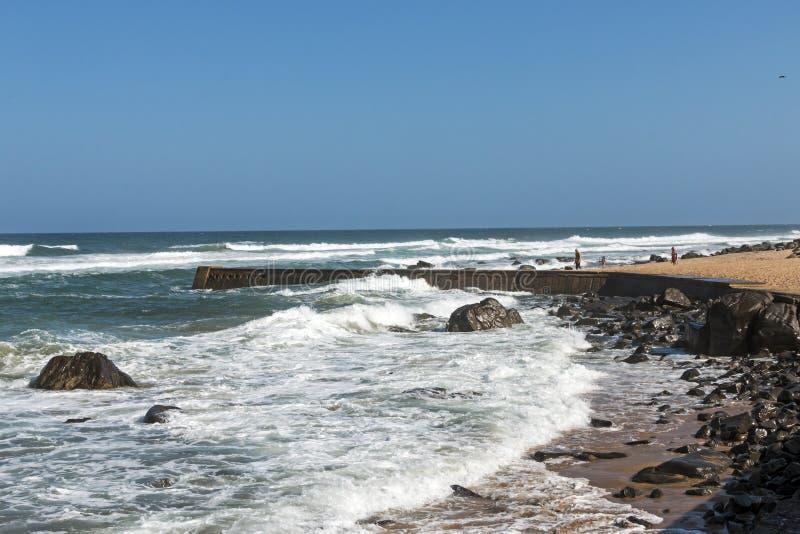 Curved Concrete Pier at Rocky Umkomaas Beach. UMKOMAAS, DURBAN, SOUTH AFRICA - DECEMBER 3, 2016: Three unknown people at curved concrete pier at rocky Umkomaas stock photography