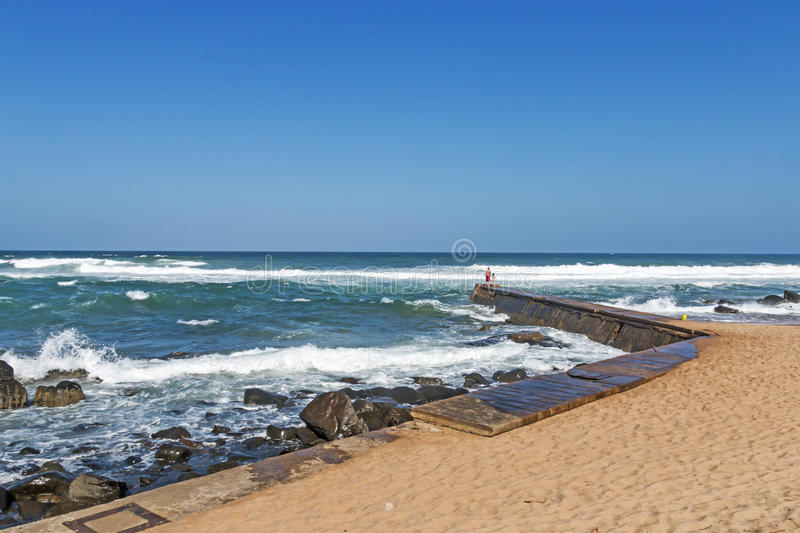 Curved Concrete Pier at Rocky Umkomaas Beach. UMKOMAAS, DURBAN, SOUTH AFRICA - DECEMBER 3, 2016: Unknown adult and child on curved concrete pier at rocky stock photography