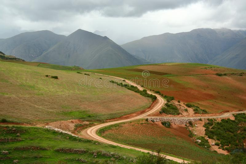 S curved country road cut deep through agriculture area into the valley of Andes mountains, Cusco, Peru royalty free stock photo