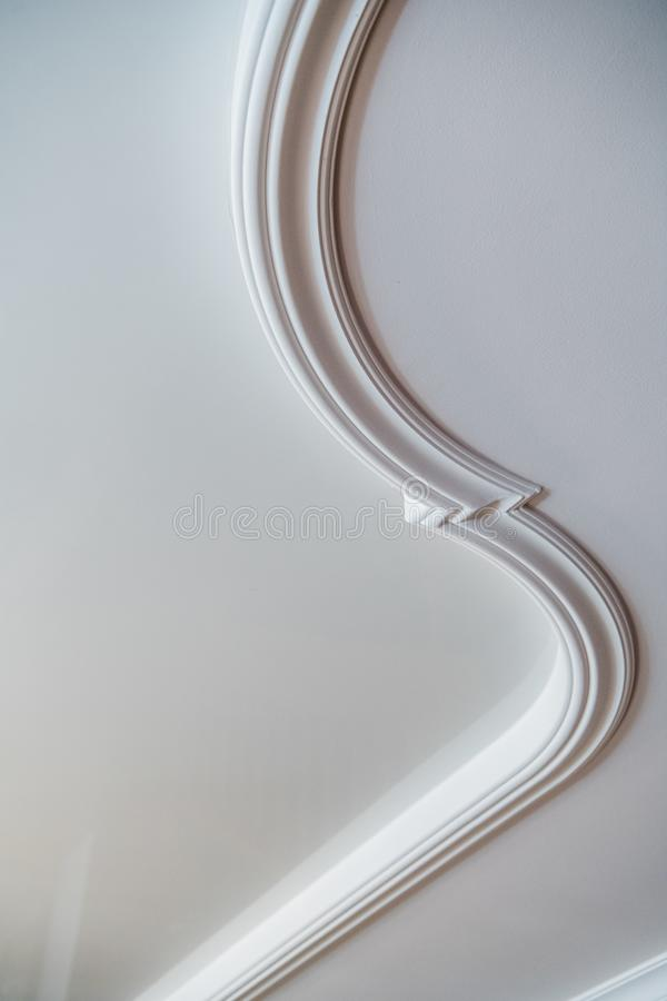 Curved decorative clay stucco relief molding on white ceiling in abstract classical style interior stock image