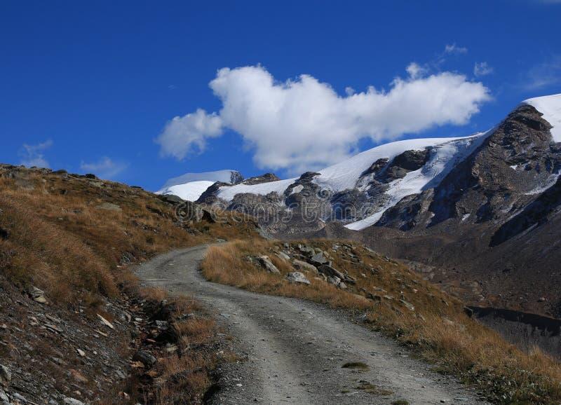 Curved gravel road in Zermatt. Findel glacier. stock photos
