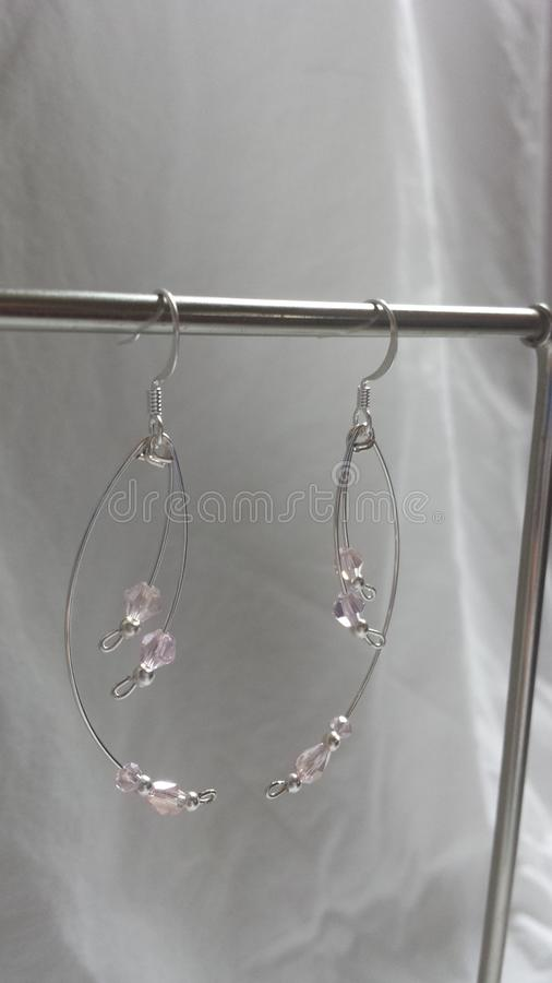 Curved light pale pink crystal and pearl drop style earrings silver plated. These beautiful earrings will accent any outfit. Hand made and designed by Amanda royalty free stock photography