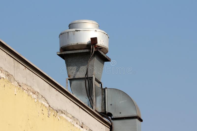 Curved metal pipe with insulation and commercial kitchen exhaust fan on top mounted on side of building wall stock image