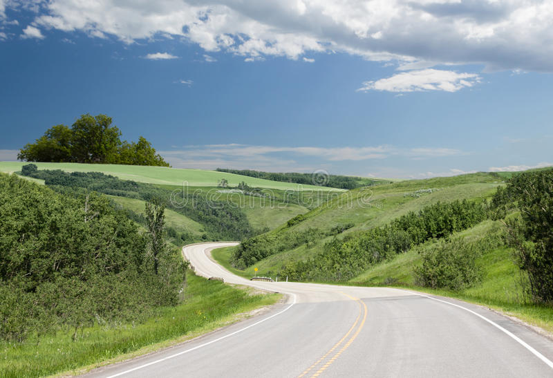 Curved paved highway winding through green hills. A curved paved highway twisting through beautiful green rolling hills with green trees under a blue sky with royalty free stock images