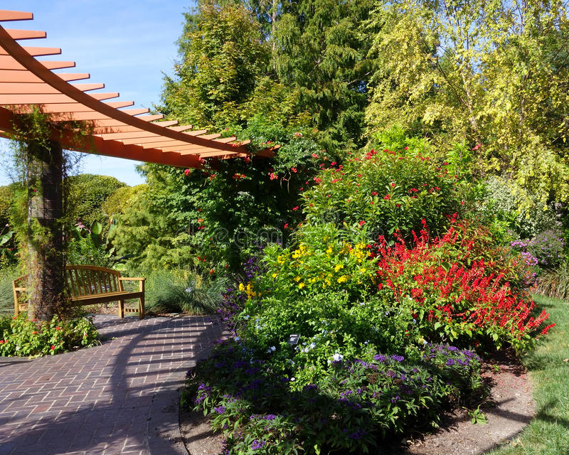 Curved pergola and garden bench stock photography