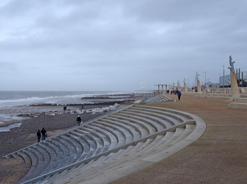 The curved promenade along the seafront at cleveleys in blackpool with steps leading to the beach with breaking waves on the shore royalty free stock photography