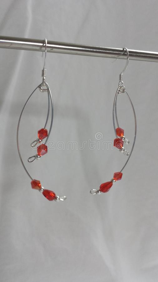 Curved red crystal and pearl drop style earrings silver plated. These beautiful earrings will accent any outfit. Hand made and designed by Amanda Smoak stock photography